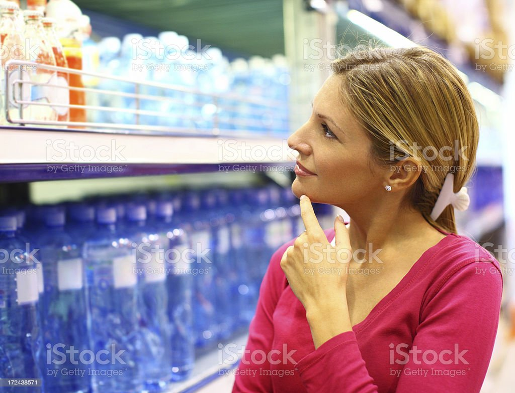 Woman choosing water in supermarket. royalty-free stock photo