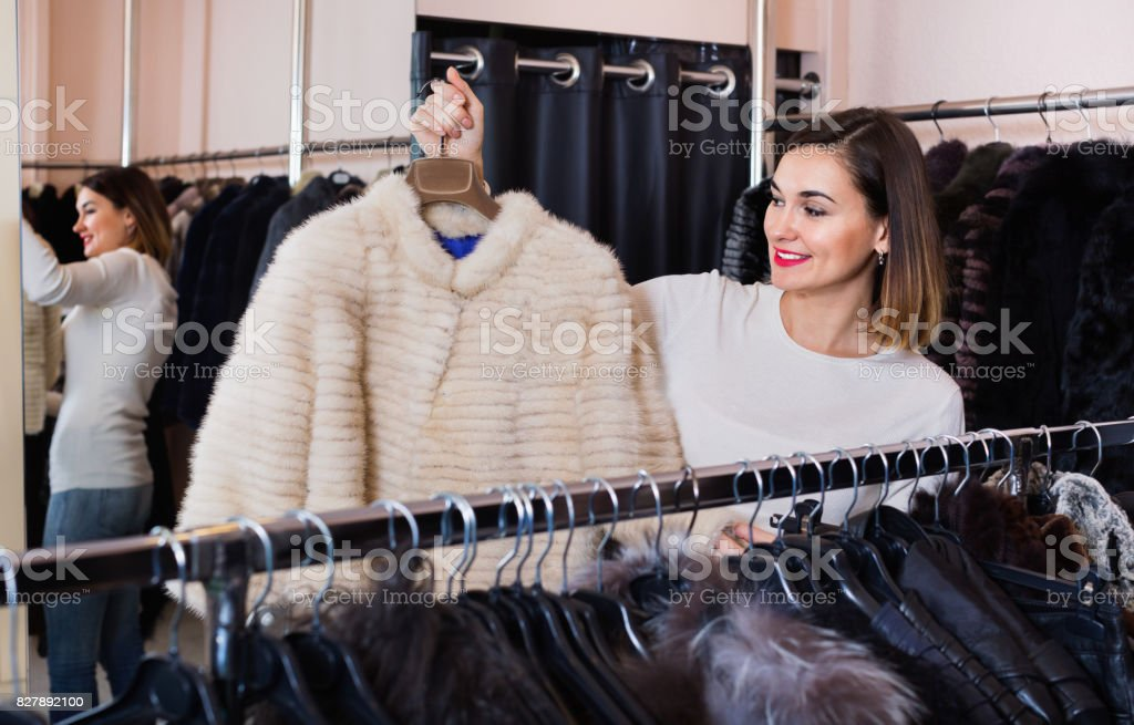 Woman choosing white mink jacket in women's cloths store stock photo