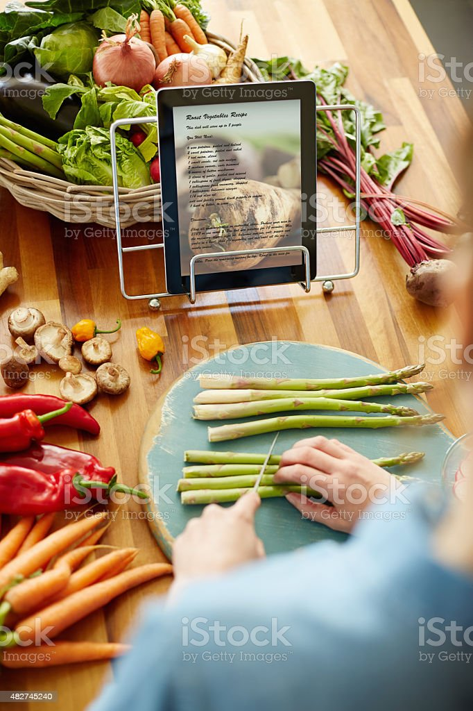 Woman chopping asparagus in front of recipe on digital tablet stock photo