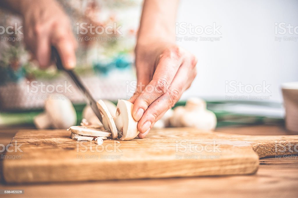 Woman chopping mushrooms with knife on cutting board. stock photo