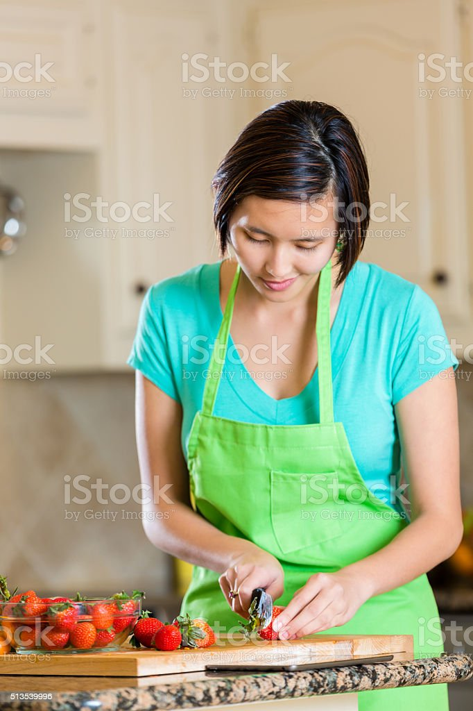 Woman chopping up strawberries in modern kitchen stock photo