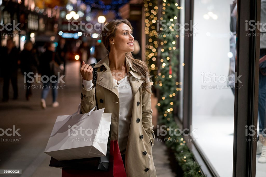 Happy woman Christmas shopping and looking at a window carrying bags