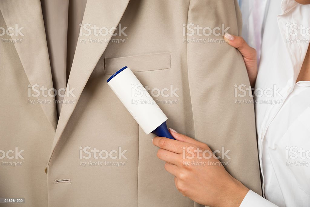 Woman Cleaning Coat With Adhesive Roller stock photo