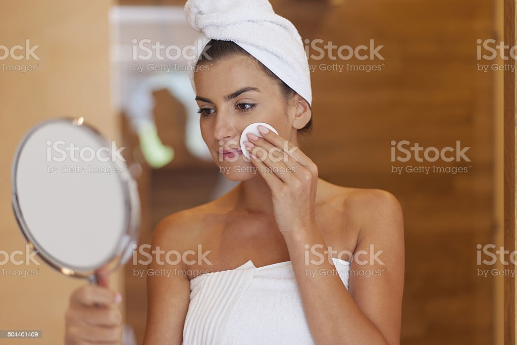 Woman cleaning face in bathroom stock photo