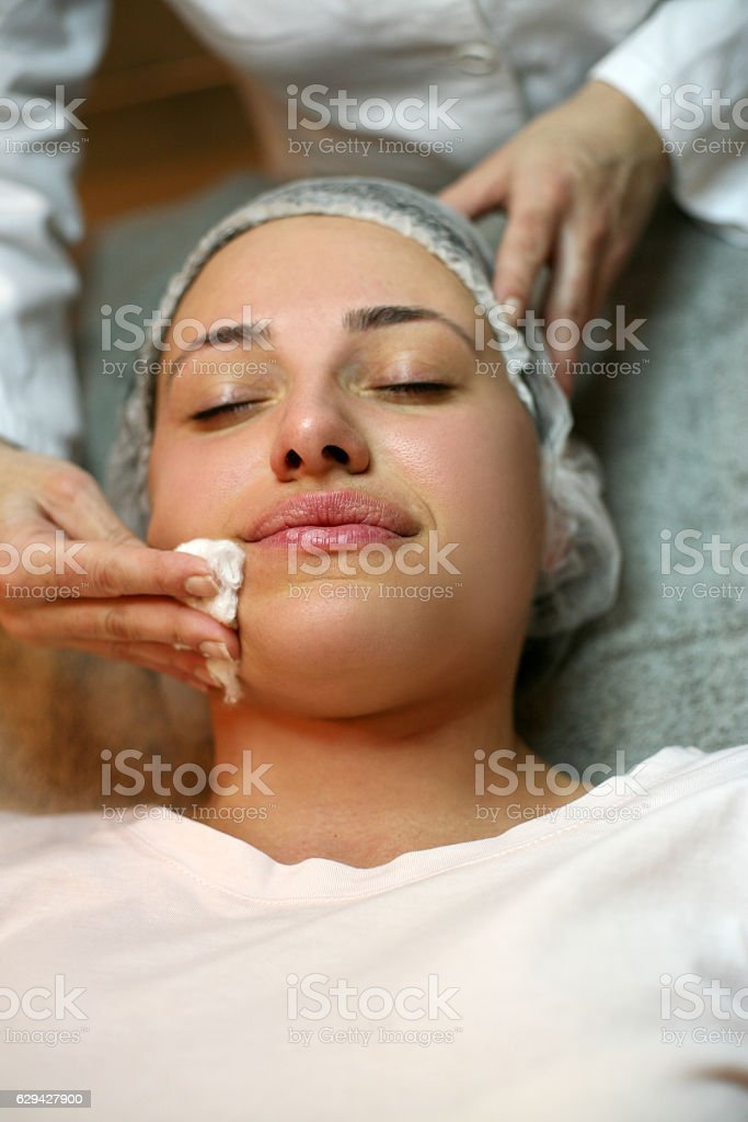 Woman cleaning face in beauty center. stock photo