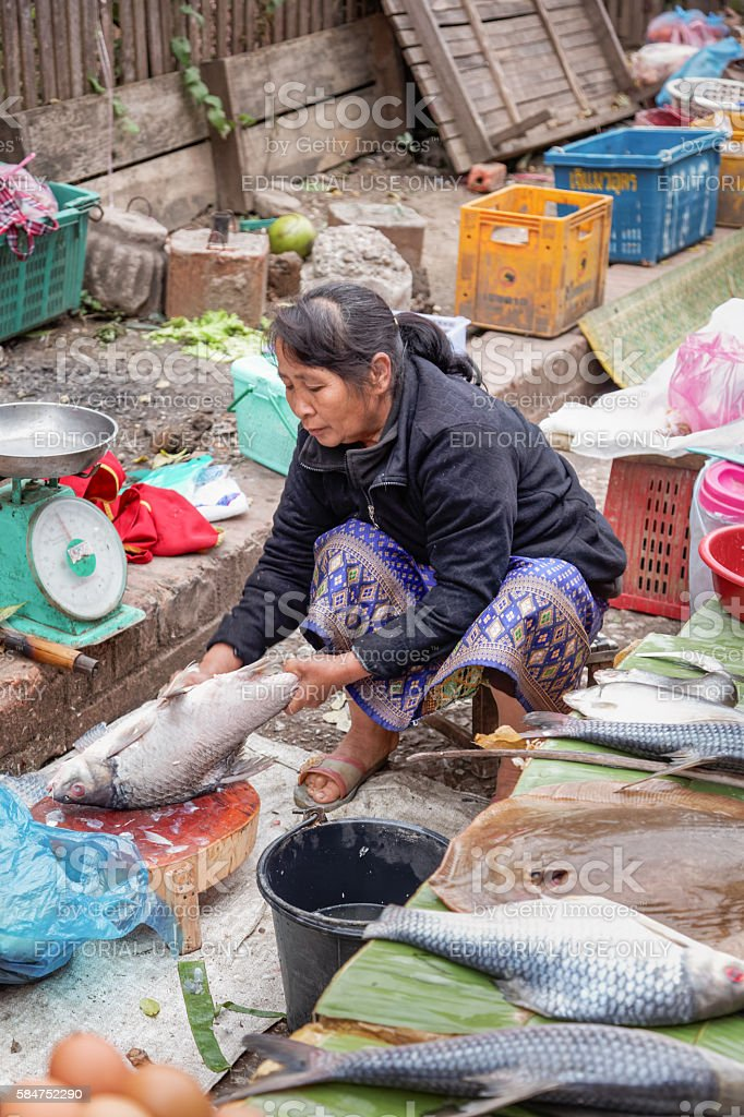 Woman cleaning fish in a street market stock photo