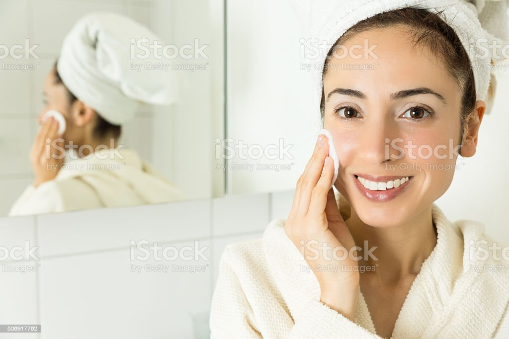 Woman cleaning her face with a cotton ball stock photo