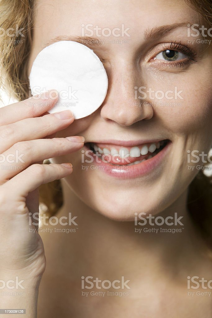 Woman Cleaning Her Face With Cotton Wool and Having Fun royalty-free stock photo