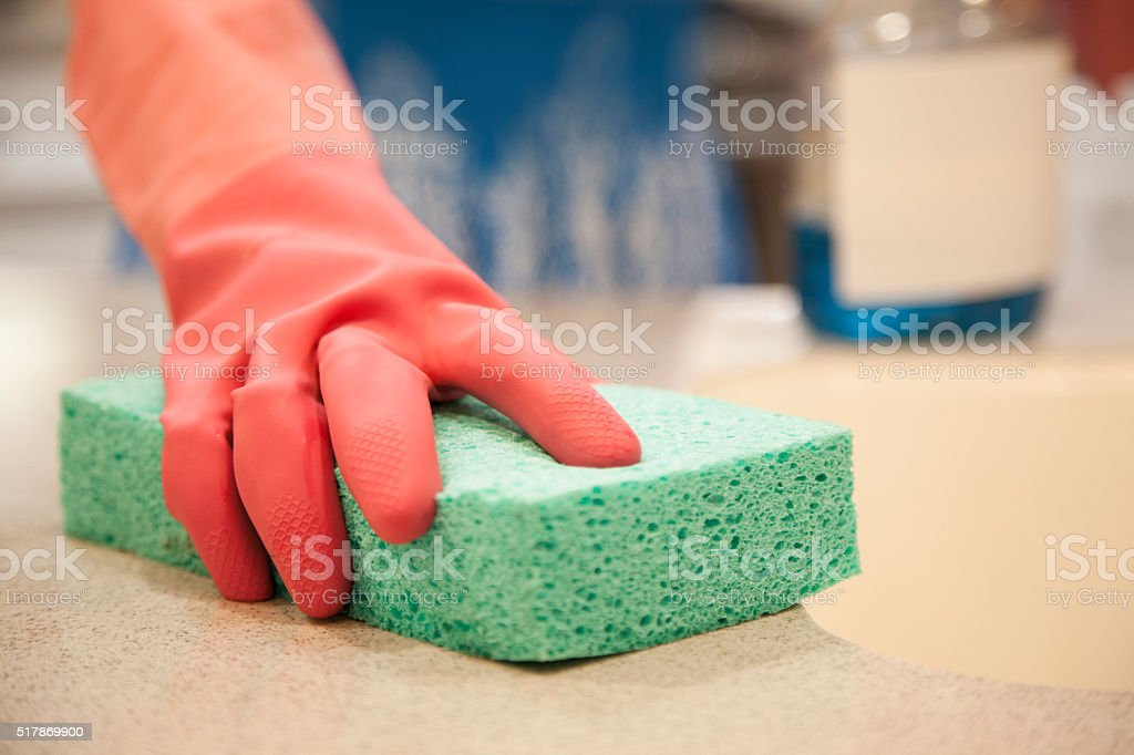 Woman cleaning her home kitchen using sponge, cleaning fluid. stock photo