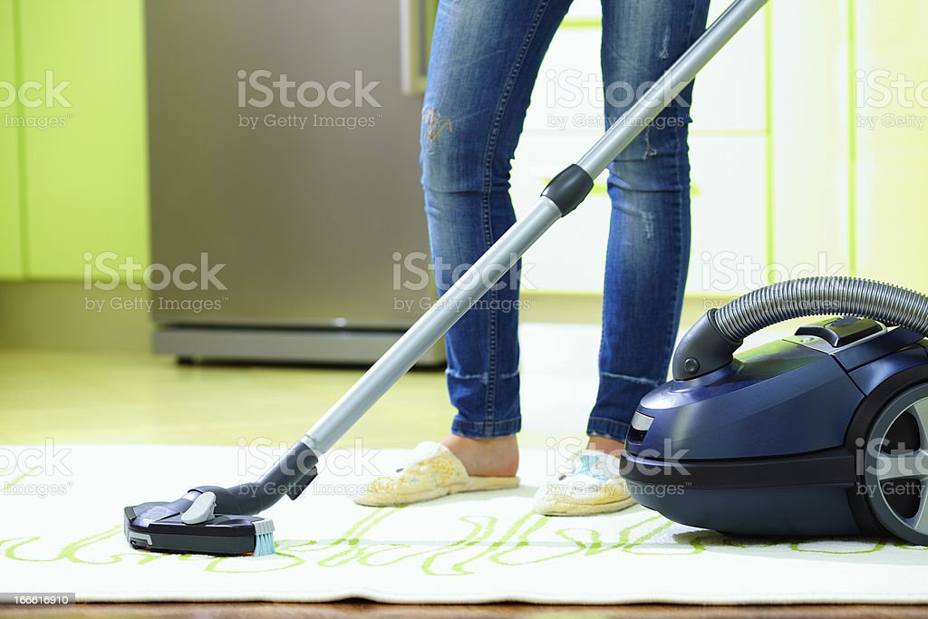 woman cleaning home with vacuum cleaner royalty-free stock photo