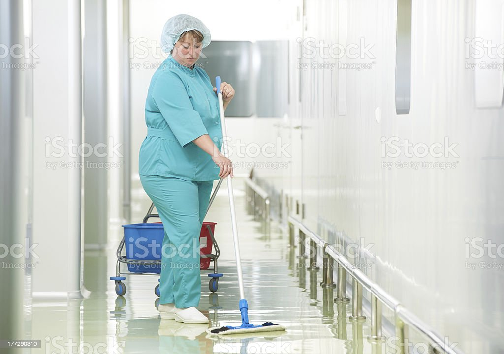 Woman cleaning hospital hall stock photo