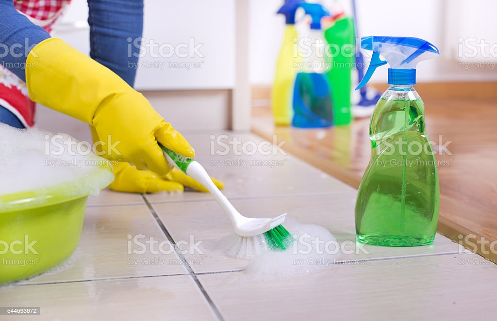 Woman cleaning kitchen floor stock photo