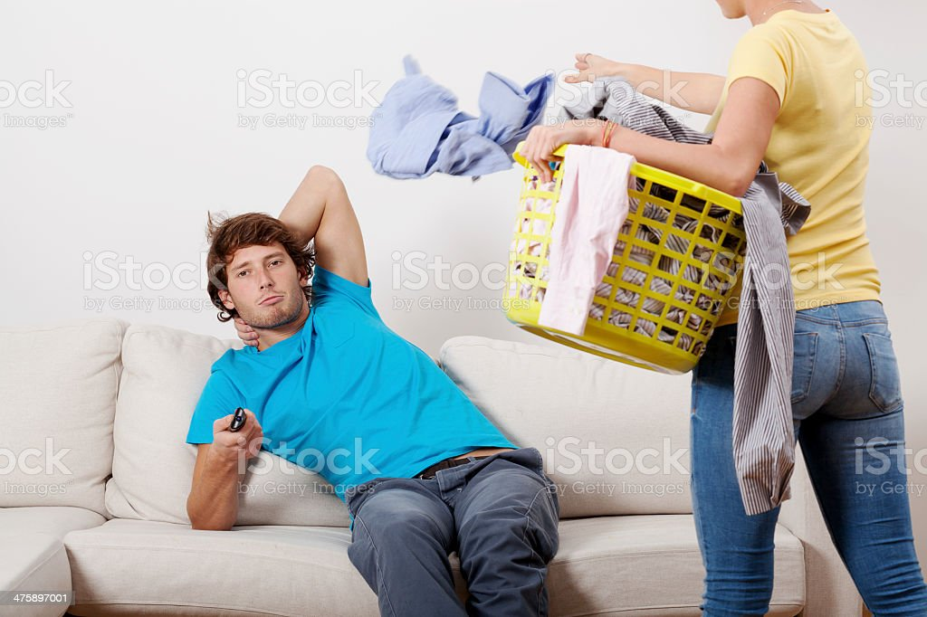 Woman cleaning man chilling stock photo