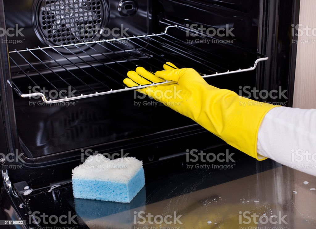 Woman cleaning oven stock photo