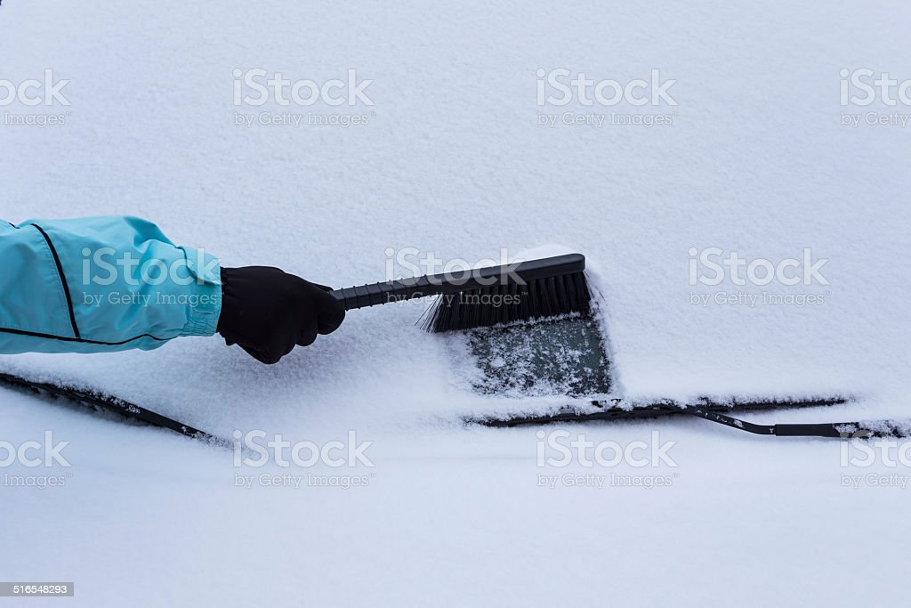 Woman cleaning snow from the car stock photo