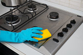 Woman cleaning stainless steel gas surface