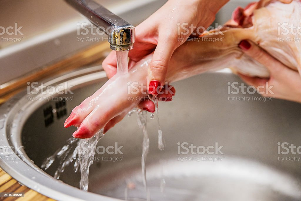 woman cleaning the raw pork for cooking at home stock photo