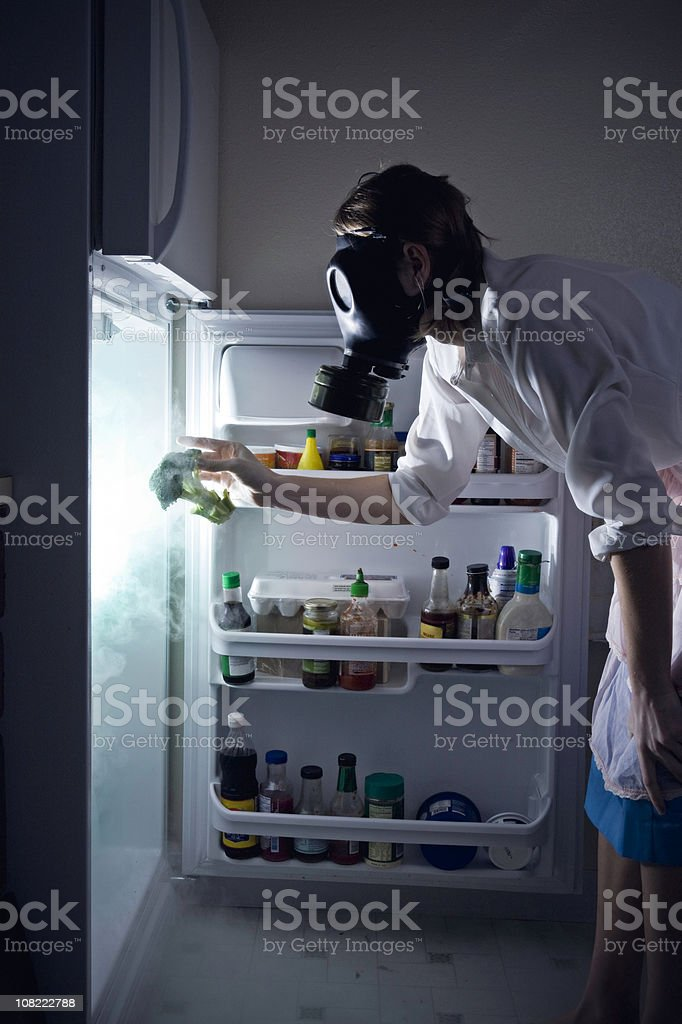 Woman Cleaning Toxic Waste Glowing Fridge stock photo