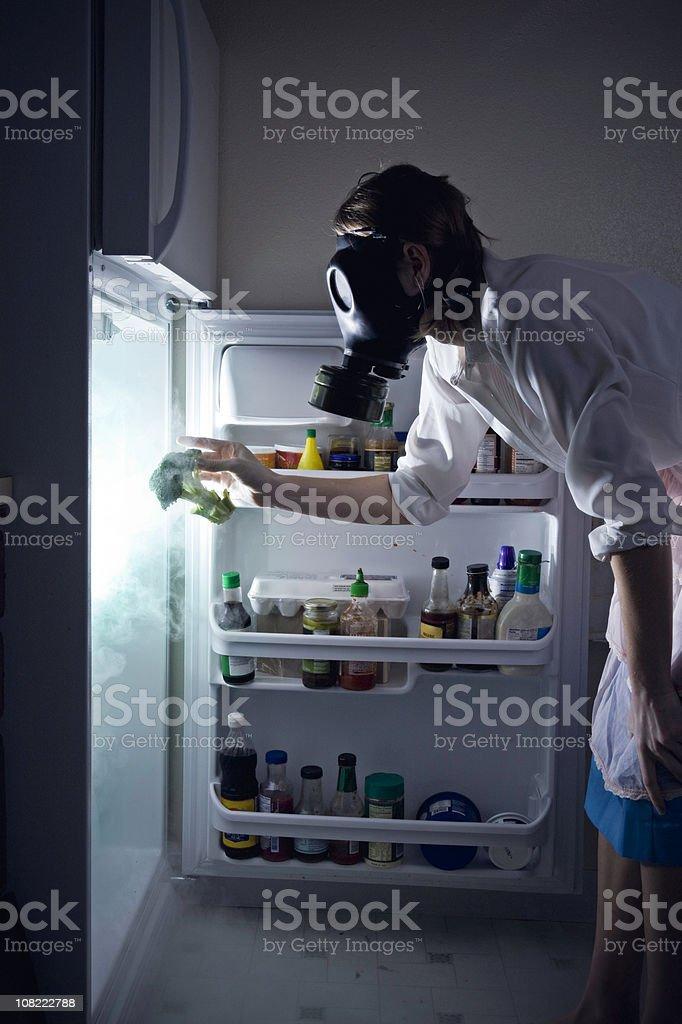 Woman Cleaning Toxic Waste Glowing Fridge stock photo