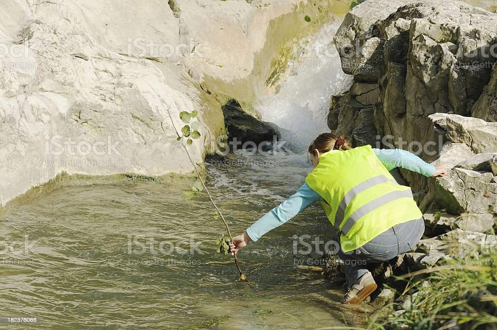 woman cleaning up river stock photo