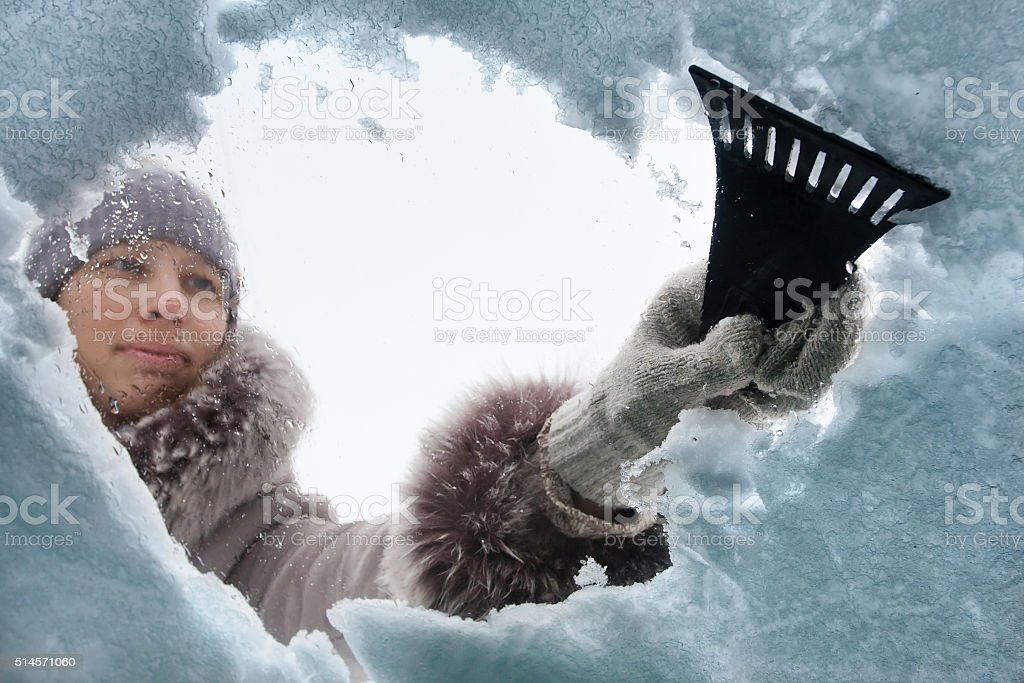 woman cleaning window of car from the snow with scraper stock photo