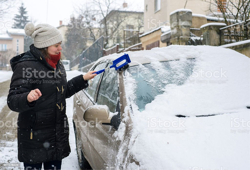 Woman cleans snow car stock photo