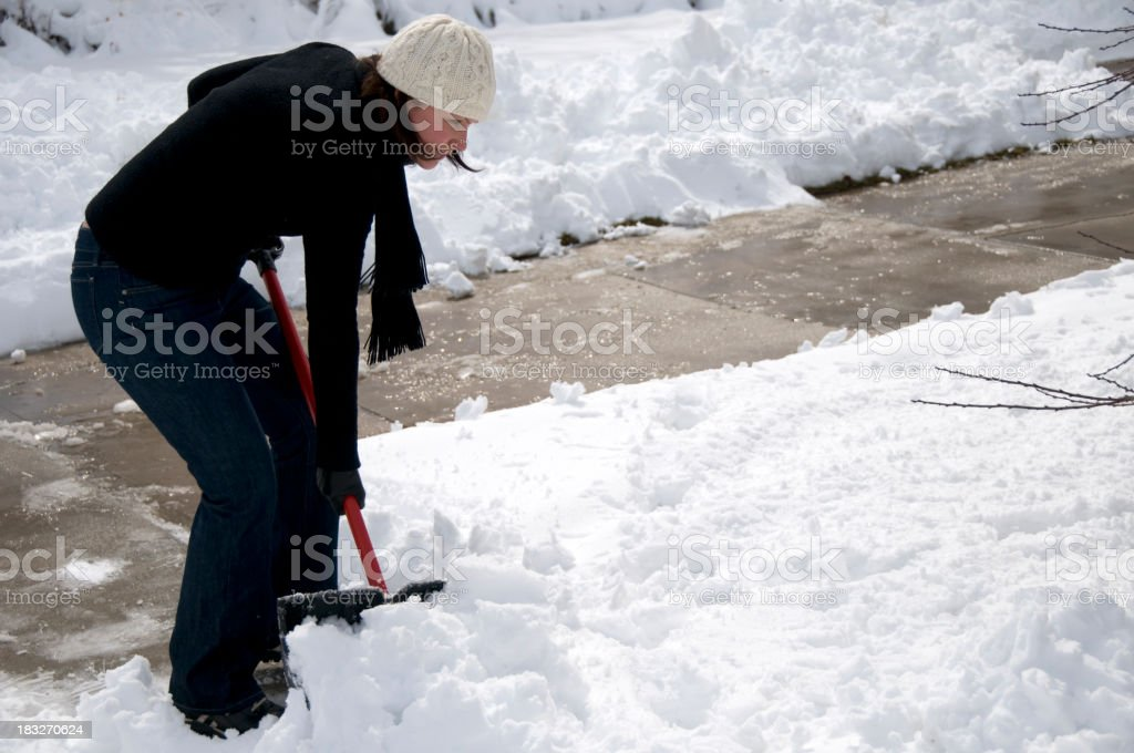 Woman Clearing Snow from Driveway stock photo