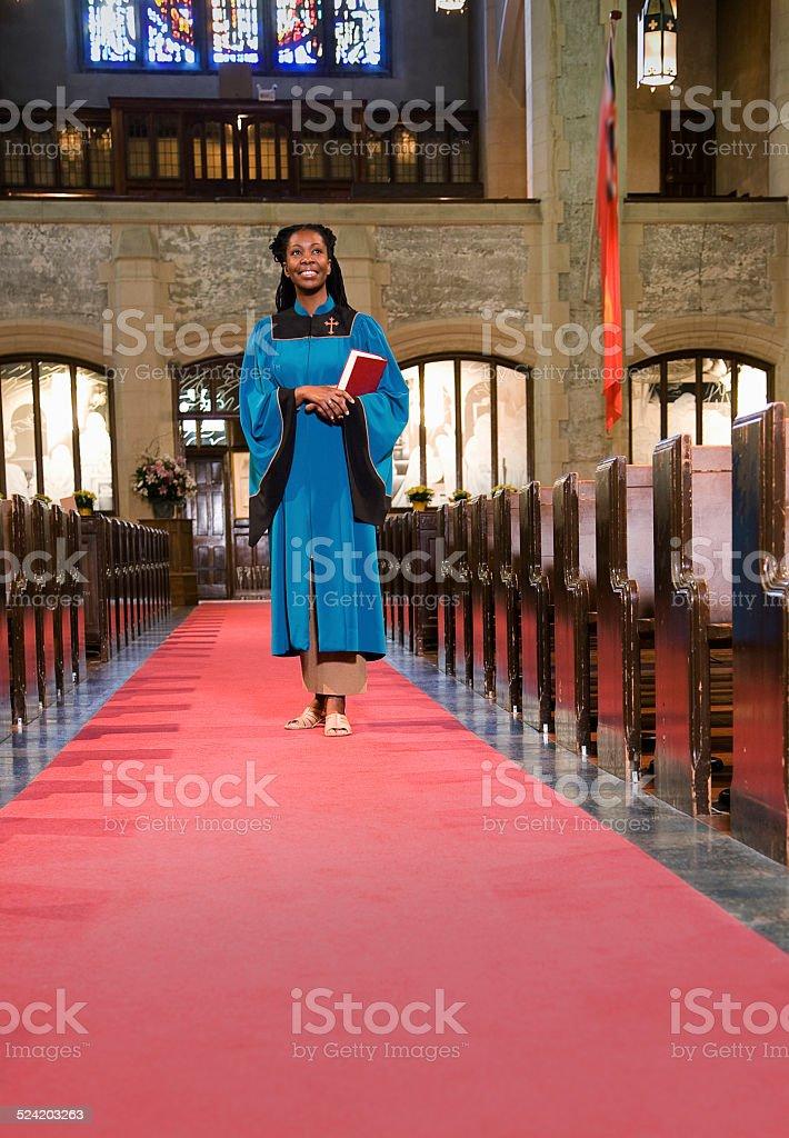 Woman Clergy Member Walking Down Church Aisle stock photo