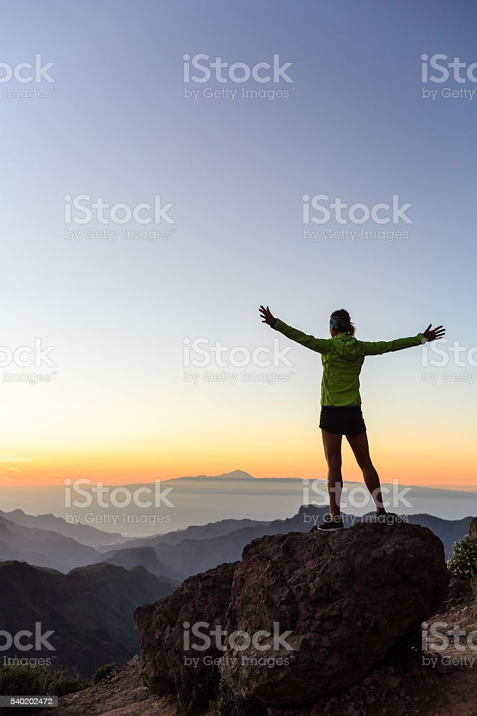Woman climber success silhouette in inspiring mountains stock photo