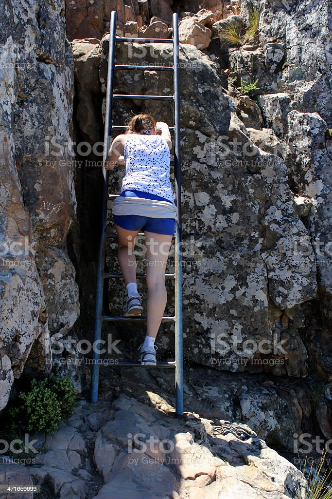 Woman climbing a ladder royalty-free stock photo