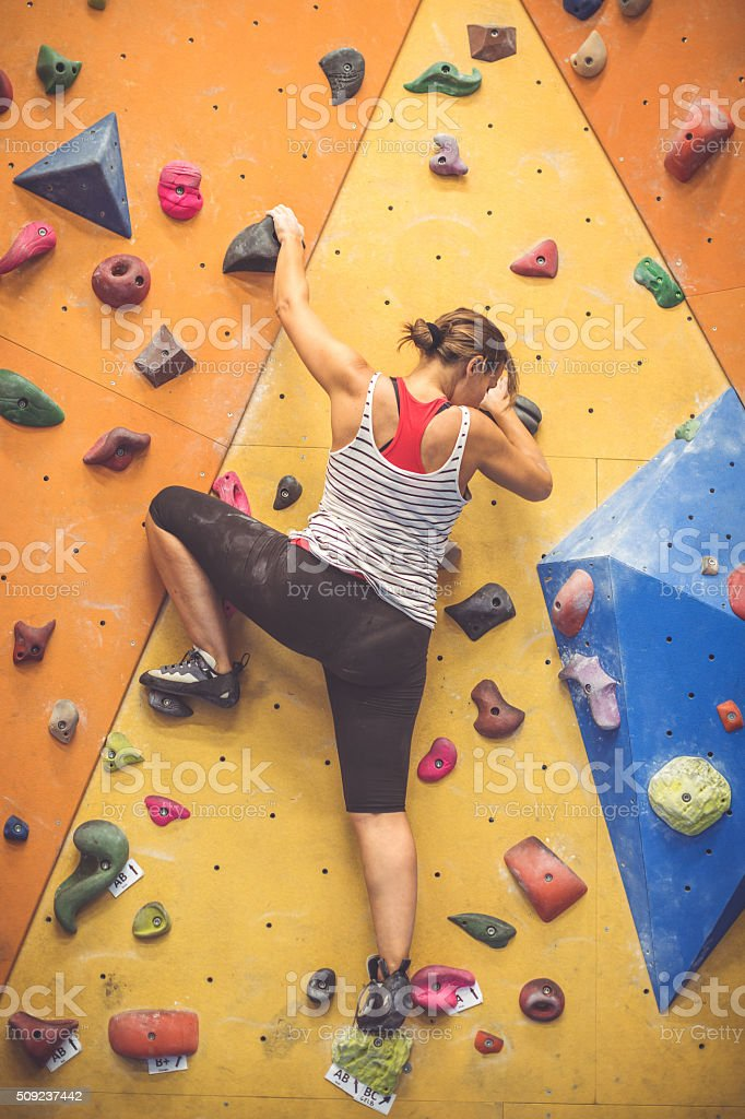 Woman climbing and bouldering indoor stock photo