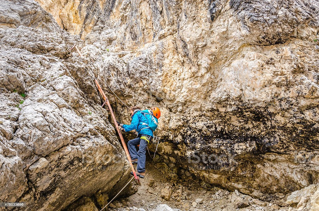 Woman climbing on metal ladder in via ferrata stock photo