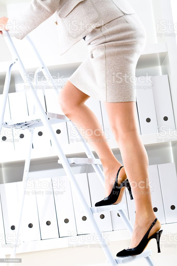 A woman climbing steps to reach something in an archive royalty-free stock photo