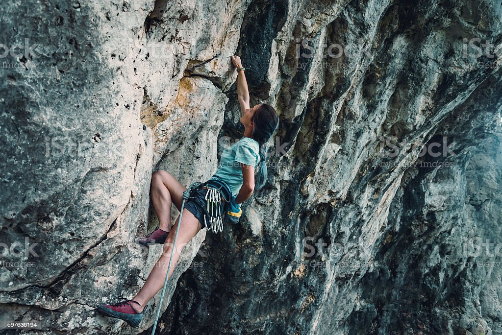 Woman climbing the rock wall stock photo