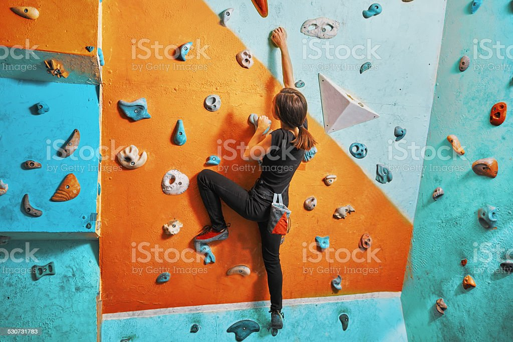 Woman climbing up on practice wall stock photo
