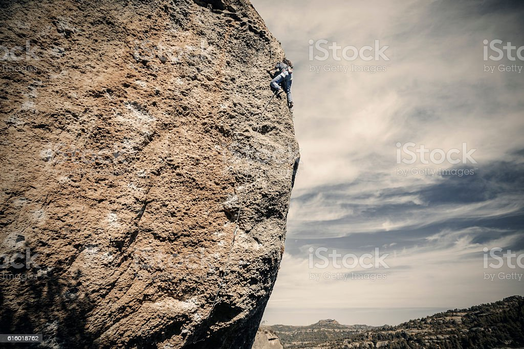 Woman climbing up rock stock photo