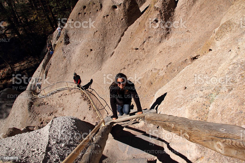 Woman Climbs Ladder stock photo