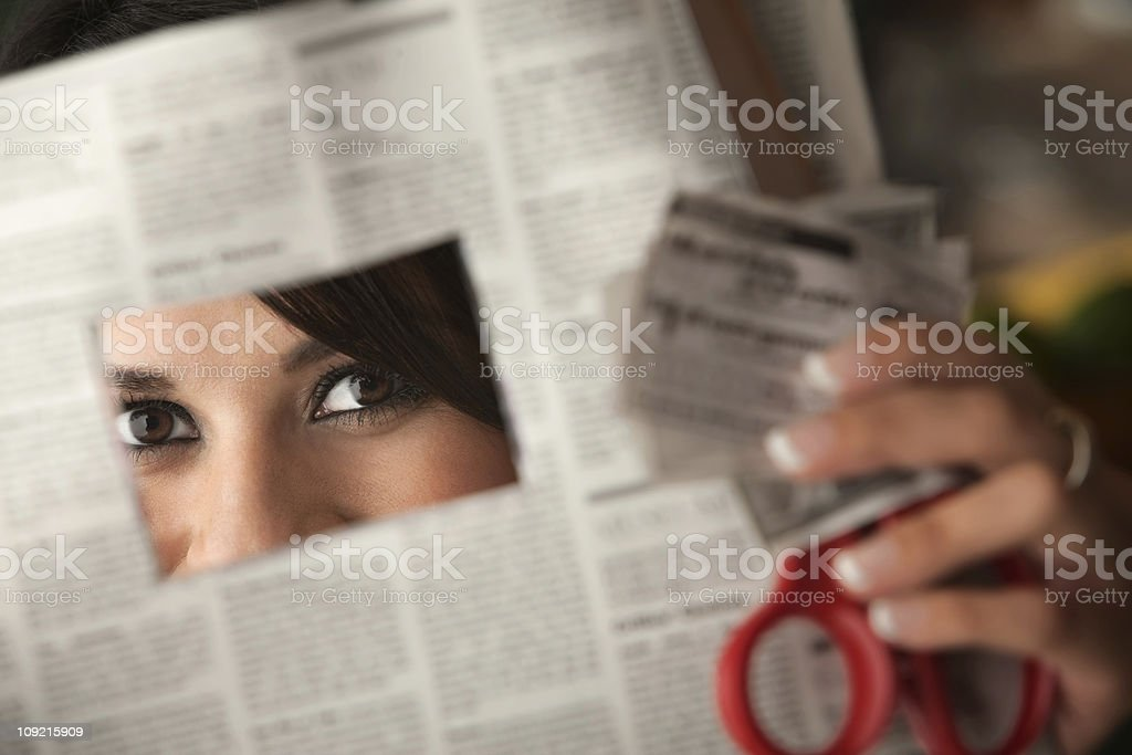 Woman clipping coupons out of newspaper with red scissors stock photo