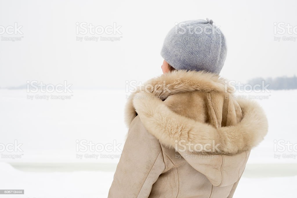 Woman Close to the Frozen River in Winter stock photo