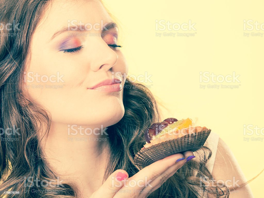 woman closed eyes holds cake in hand stock photo