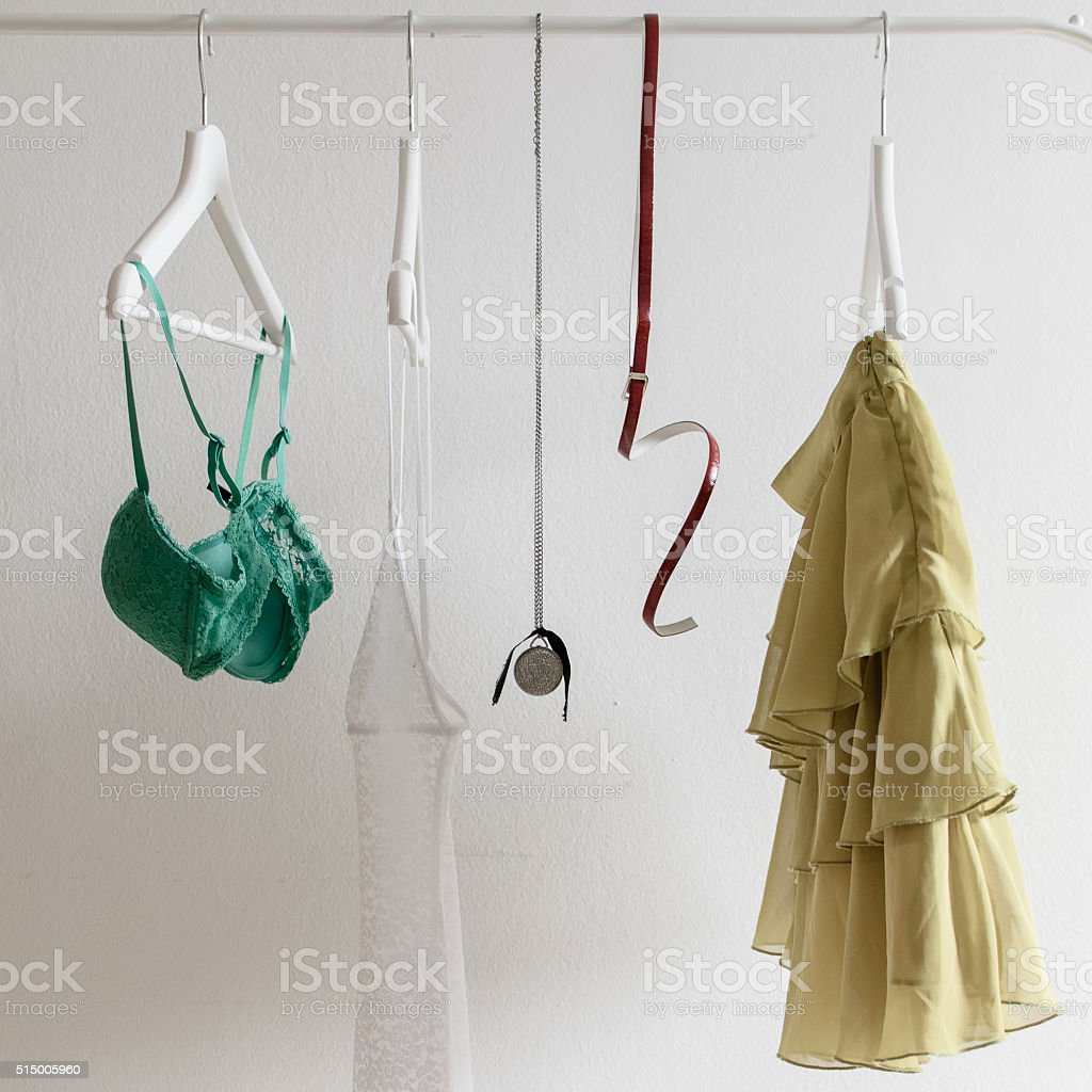 Woman clothes hanging over white wall stock photo