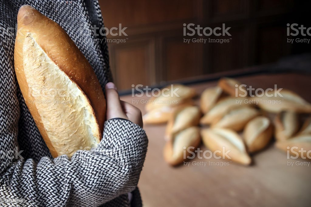 Woman clutching loaf of bread with background of more loaves stock photo