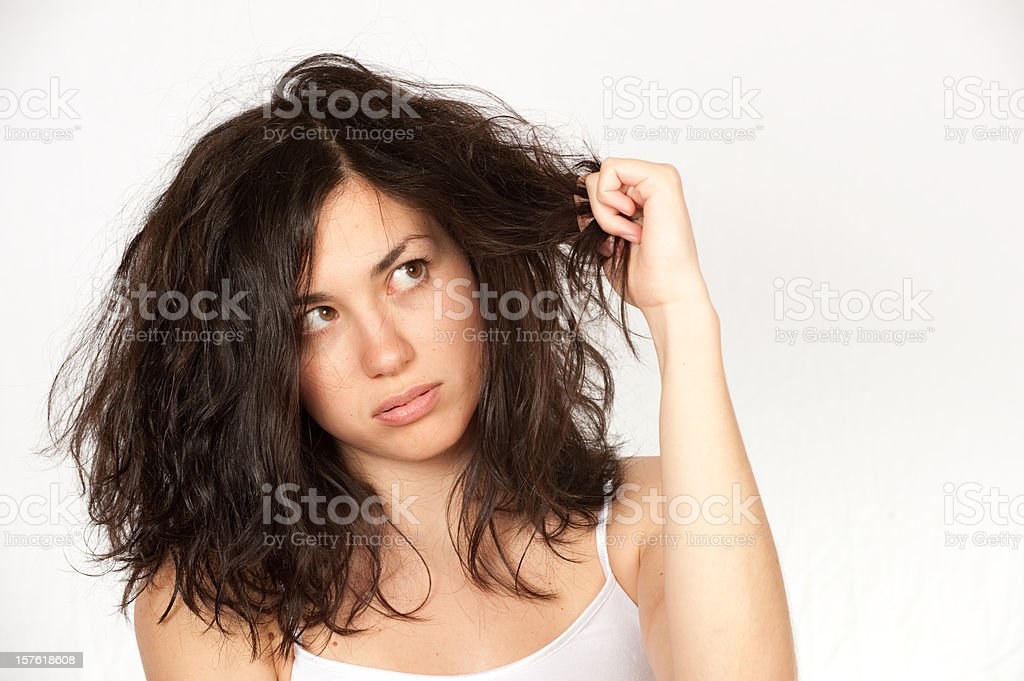 Woman clutching wavy dark hair over a white background stock photo