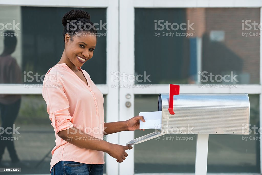 Woman Collecting Her Mail From Mailbox stock photo