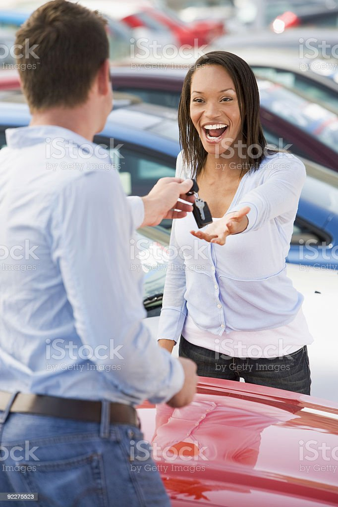 Woman collecting keys to new car royalty-free stock photo