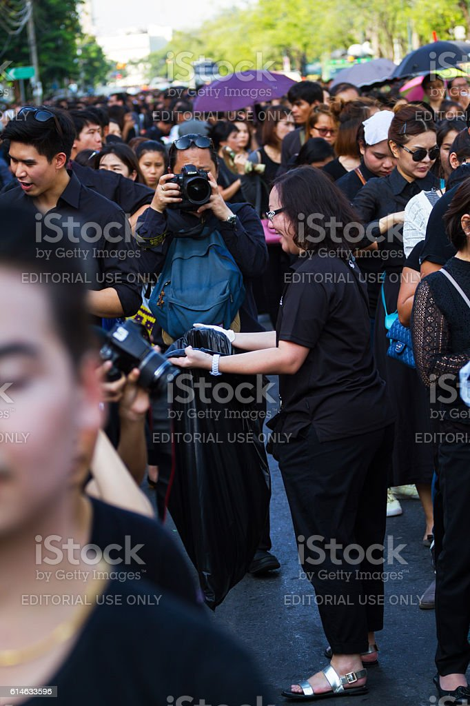 Woman collecting waste in condolencing queue of thai people stock photo