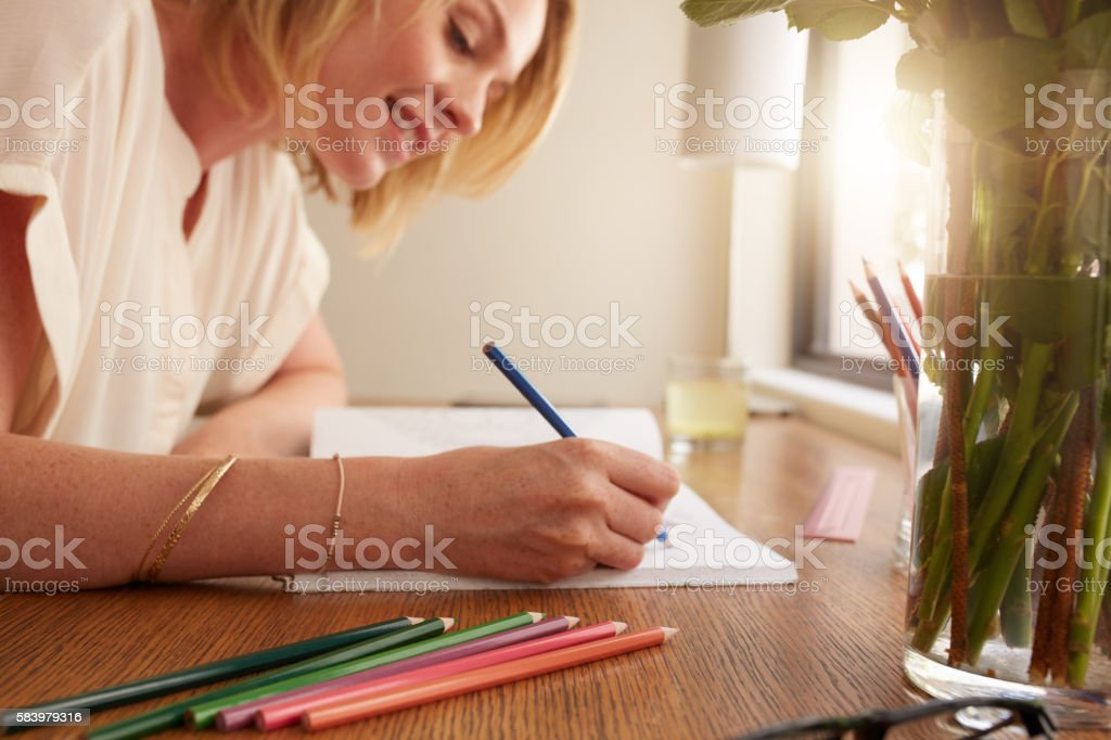 Woman coloring an adult coloring book with pencils stock photo