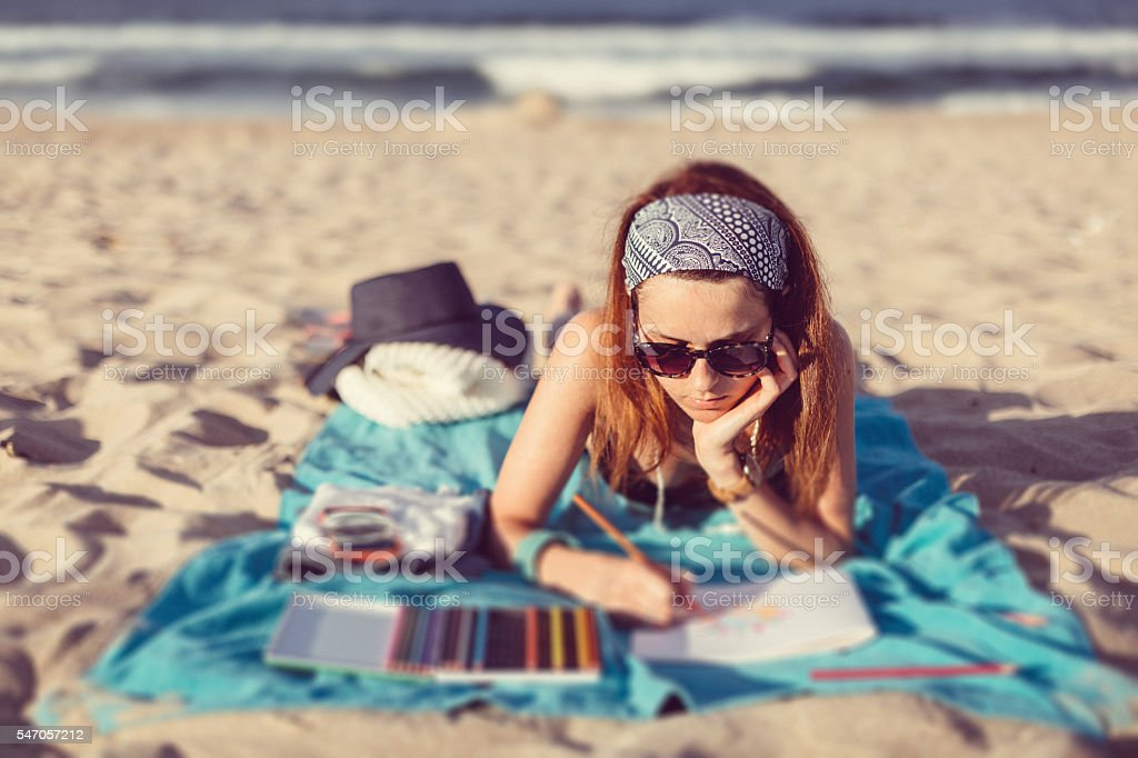 Woman coloring anti stress book at the beach stock photo