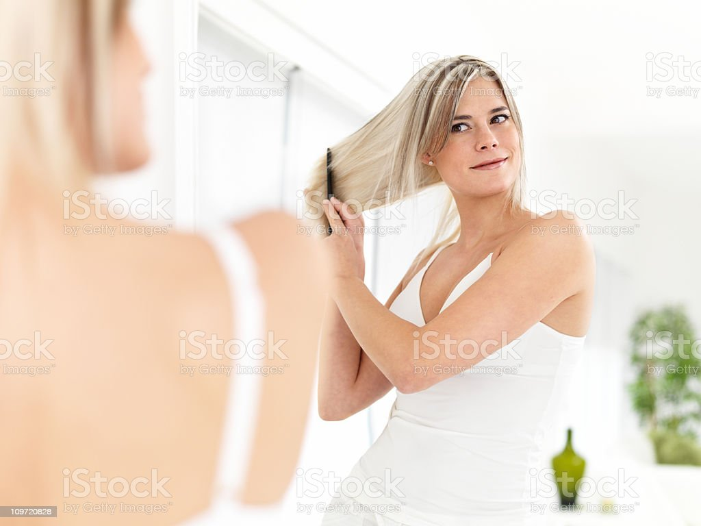 Woman combing hair in mirror royalty-free stock photo