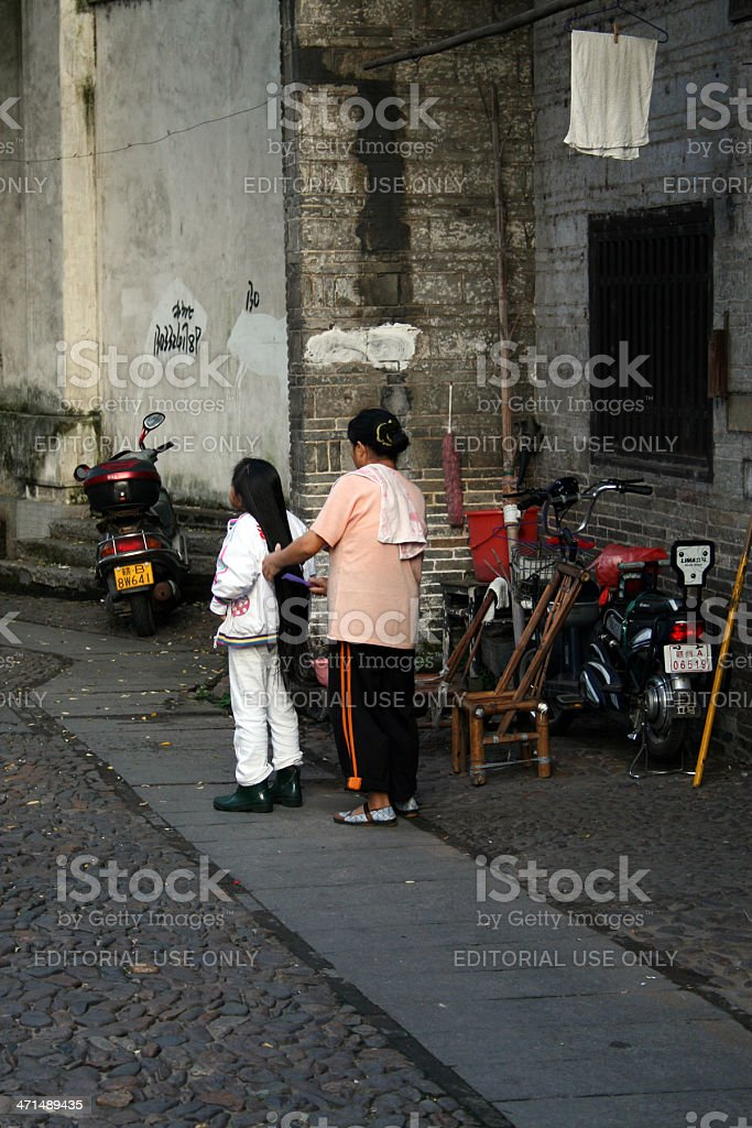Woman Combing Her Daughters Long Hair, China royalty-free stock photo